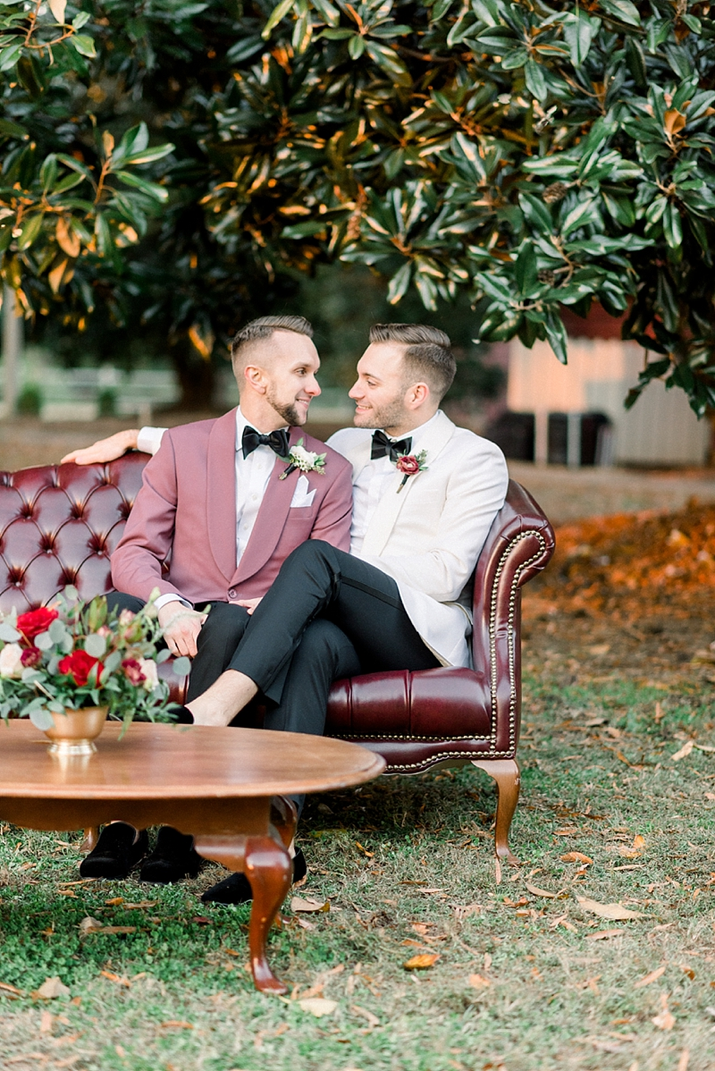 Two modern classic grooms on vintage leather rental sofa at Seven Springs in Richmond Virginia