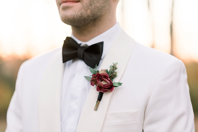 Simple dark red boutonniere on white dinner tuxedo jacket for rustic fall wedding in Virginia