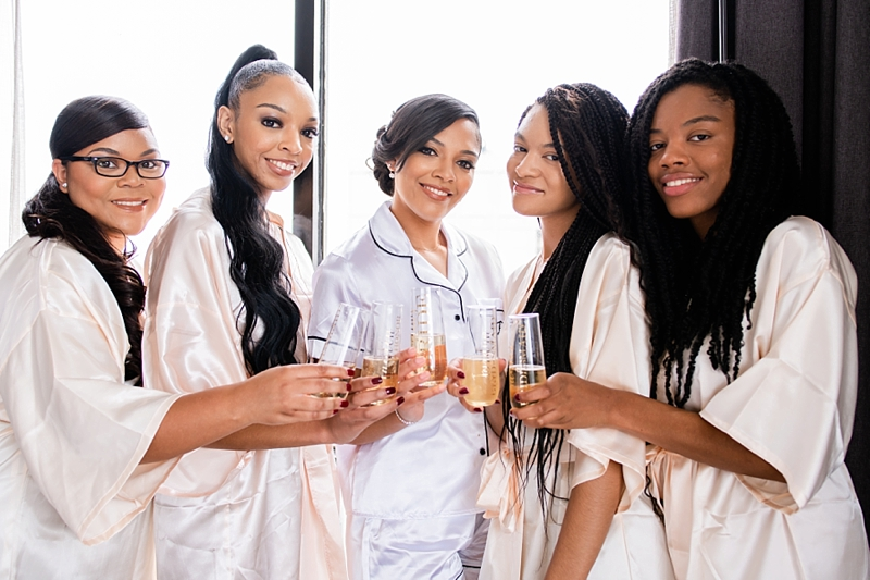 Elegant black bride and her bridesmaids share a getting ready champagne toast in matching satin white and pink pajamas in Richmond Virginia