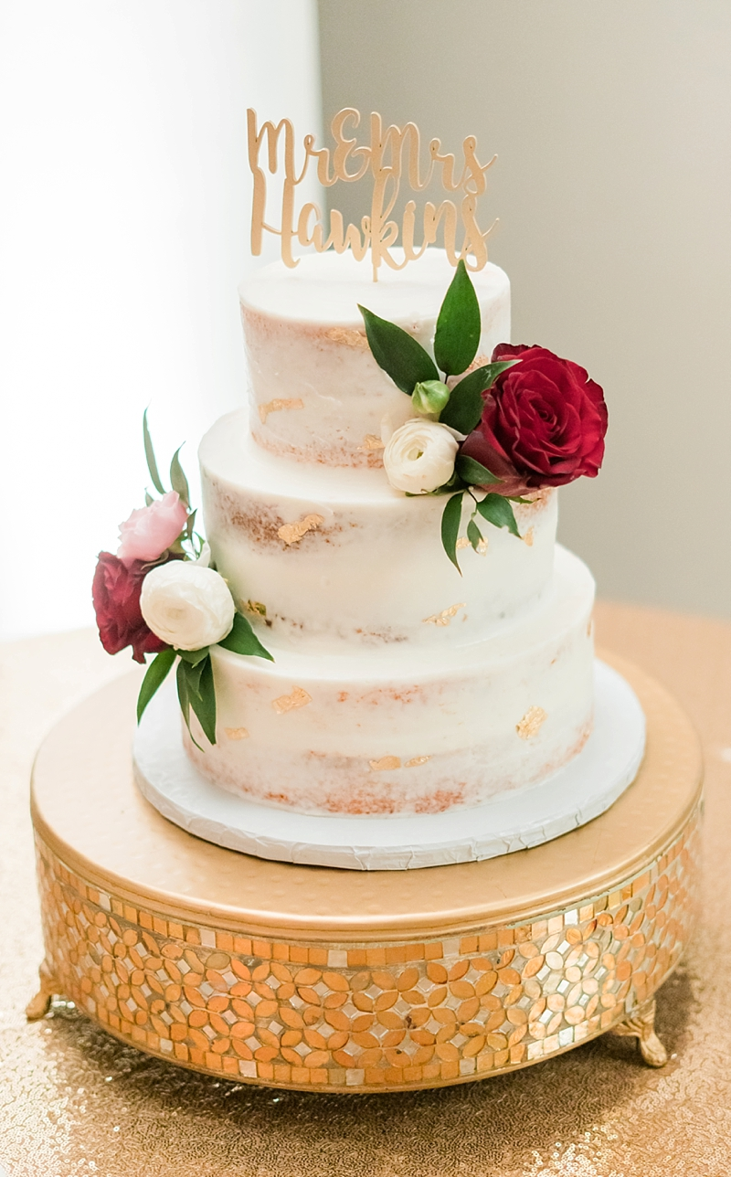 Three tiered semi naked wedding cake with gold flakes and custom cake topper and floral decorations on a mirrored gold cake stand for a classic wedding in Richmond Virginia