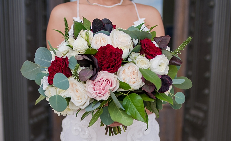 Lush wedding bouquet with red and pink roses and eucalyptus leaves for a Richmond Virginia wedding day