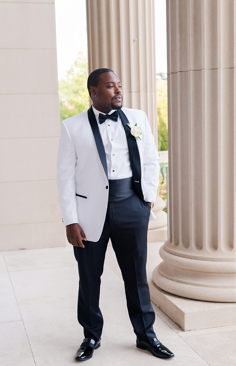 Dapper black groom in white tuxedo jacket with black satin collar and cummerbund and simple rose boutonniere for his Virginia wedding