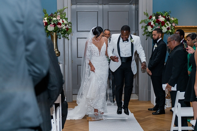 Beautiful moment of black bride and groom jumping the broom at their wedding ceremony at Virginia Museum of History and Culture in Richmond Virginia