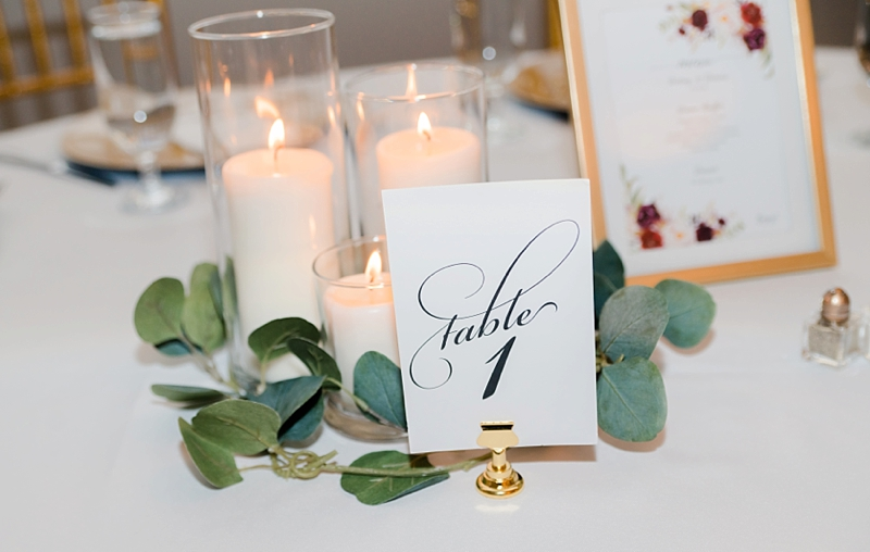 Elegant printable wedding table numbers on gold clip stand surrounded by candles and eucalyptus leaves for reception centerpiece ideas