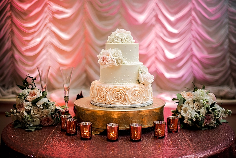 Three tiered wedding cake with dotted and rose details on top of a round gold platform cake stand and rose gold sequin tablecloth