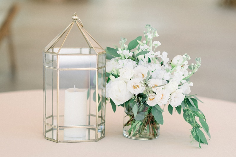 Classic modern white and gold wedding reception centerpiece idea with geometric lantern and monochromatic flowers