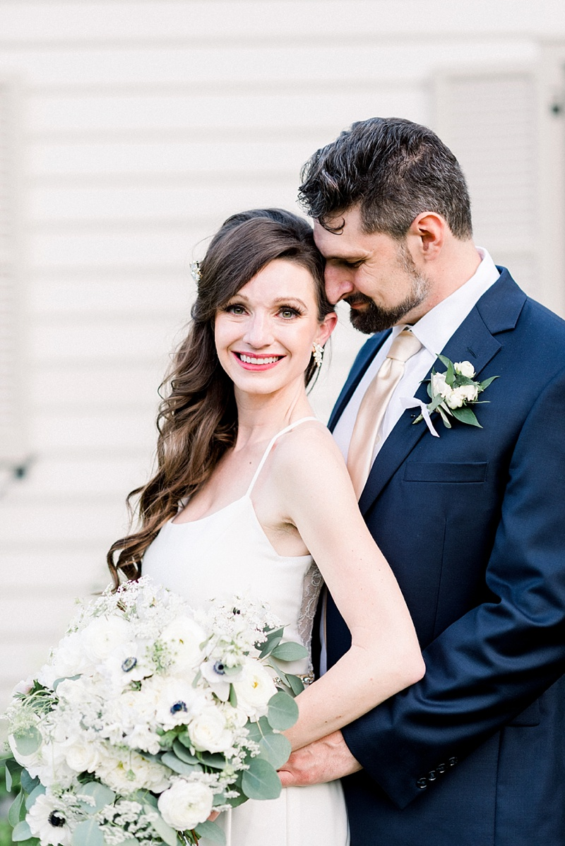 Happy bride and groom photo moment with bride wearing a classic fitted spaghetti strap gown and groom wearing gold necktie