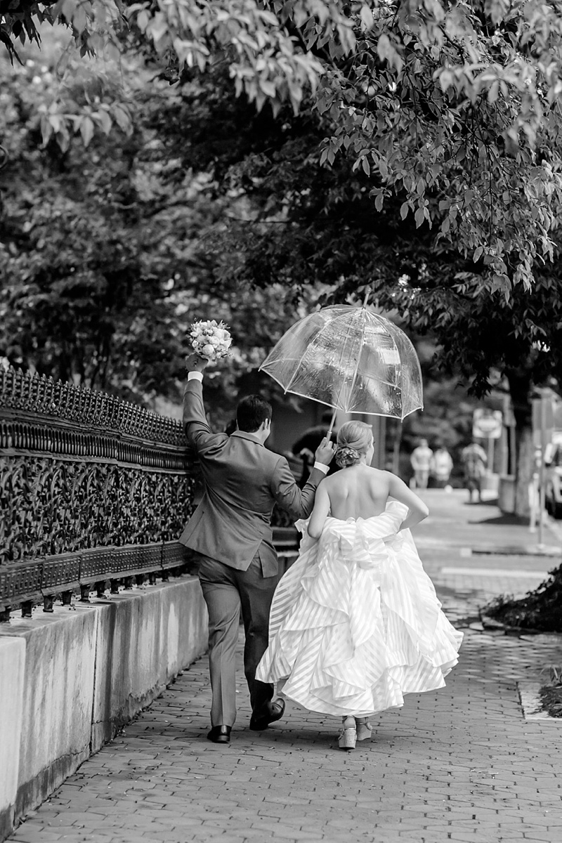 Rainy wedding day with groom holding a bubble umbrella for his bride in Richmond Virginia
