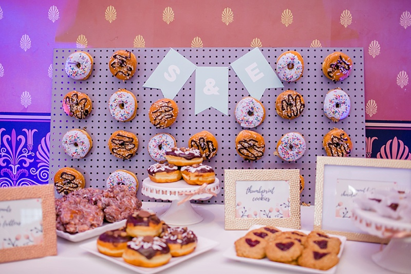Fun wedding dessert table with a donut wall and thumbprint cookies for a sweet treat
