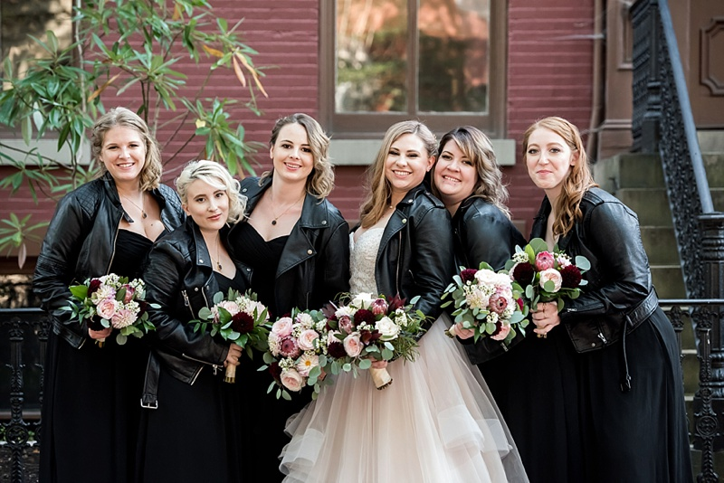 Gorgeous vintage modern wedding with bridesmaids in black dresses and black leather jackets holding fall inspired bouquets with proteas in Richmond Virginia