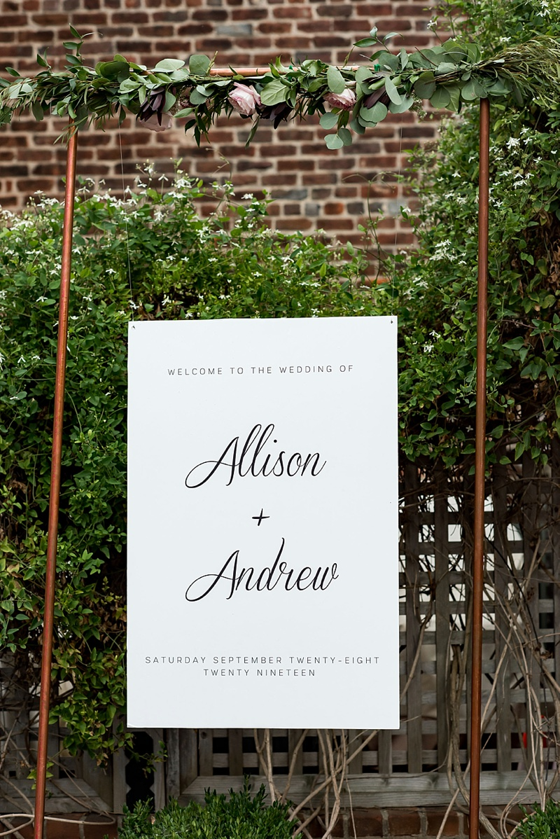 Simple and chic wedding welcome sign hanging on a copper frame with floral swag for a Richmond Virginia wedding