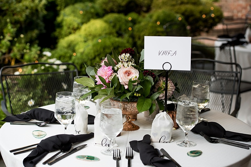 Low flower centerpiece in copper mercury vase surrounded by black flatware and napkins for vintage modern wedding reception decor ideas