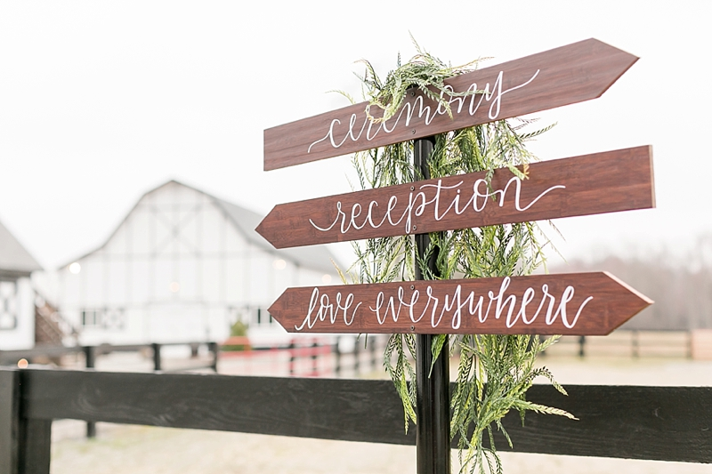 Rustic directional wedding signage in classic white calligraphy for outdoor barn wedding