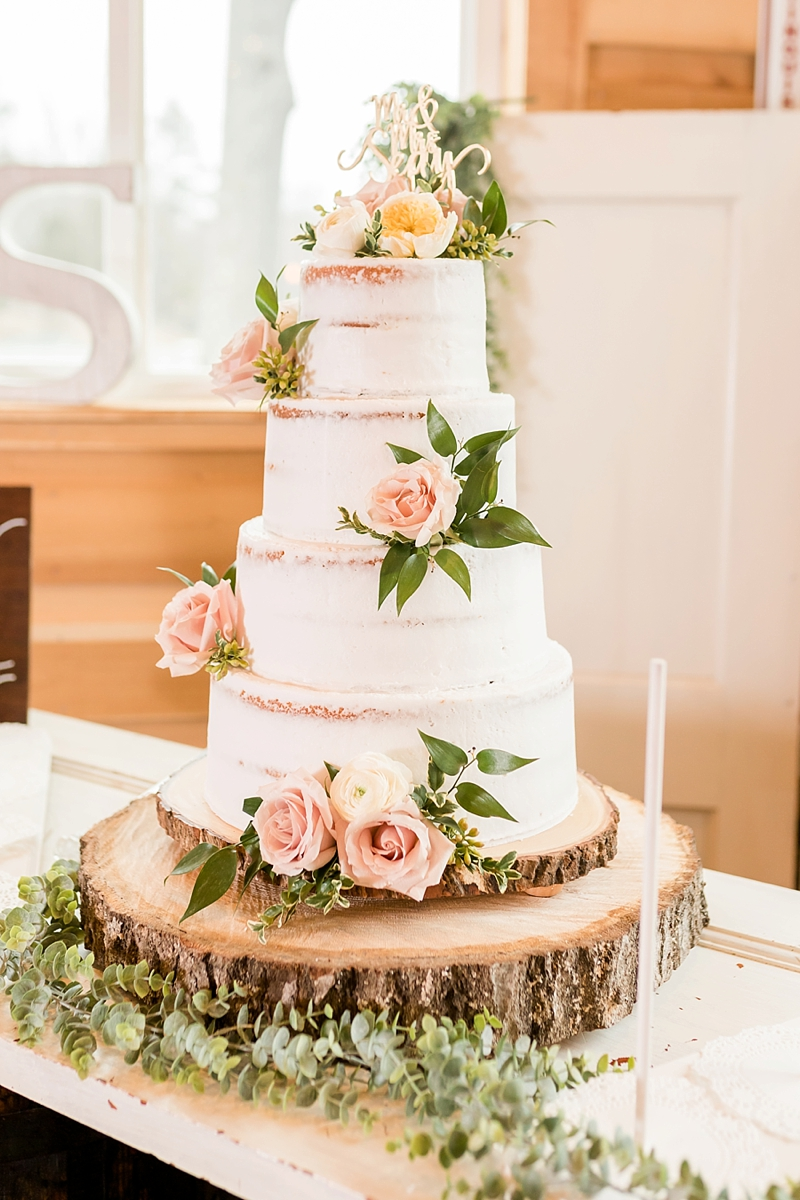 Semi naked three tiered cake with roses and gold wedding cake topper on large wood slices
