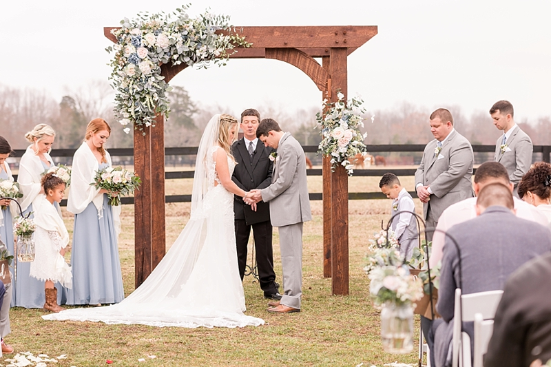 Rustic outdoor wedding ceremony with wooden arch and lush floral swag for decor