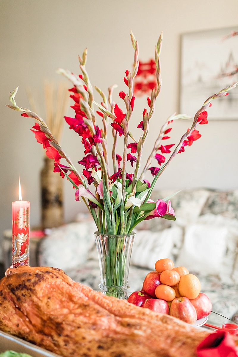 Tall red and magenta pink flowers for Chinese tea ceremony centerpiece surrounded by traditional details
