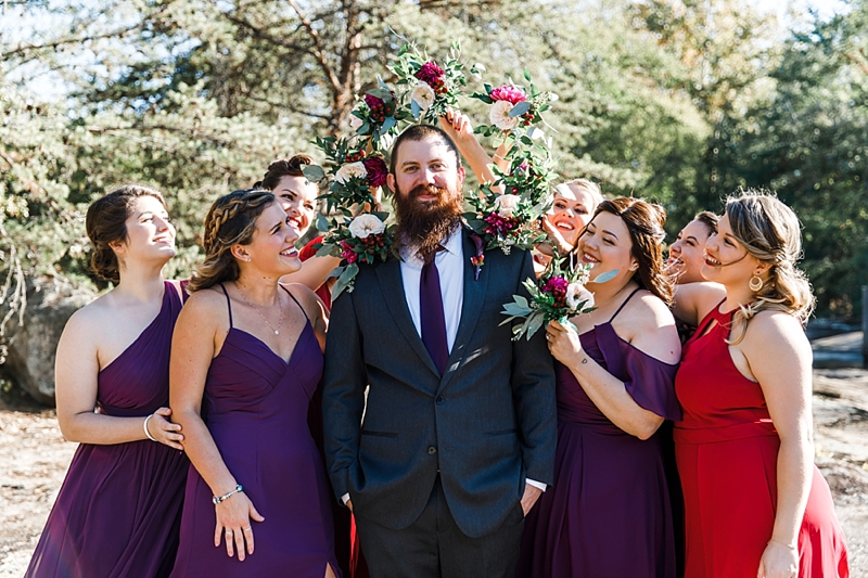 Bearded groom surrounded by happy bridesmaids in plum purple and red dresses for a Mill at Fine Creek wedding in Virginia