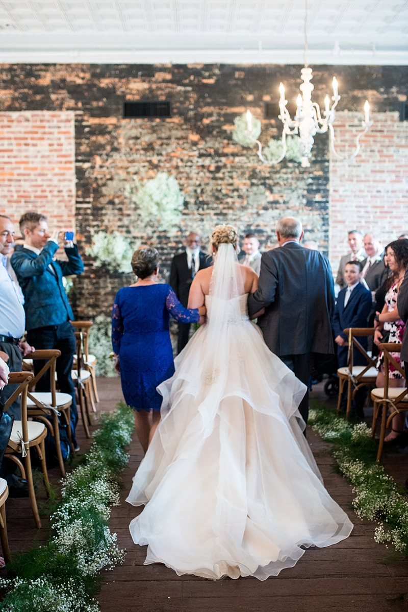 Indoor rustic wedding ceremony at Smithfield Winery with lots of babys breath flower details