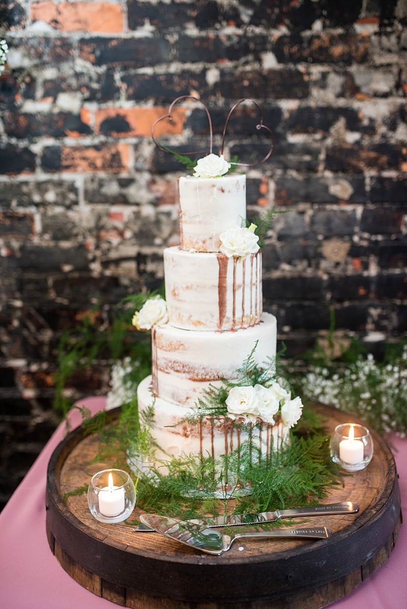 Tiered semi naked wedding cake with copper drops and copper wire hearts for its cake topper