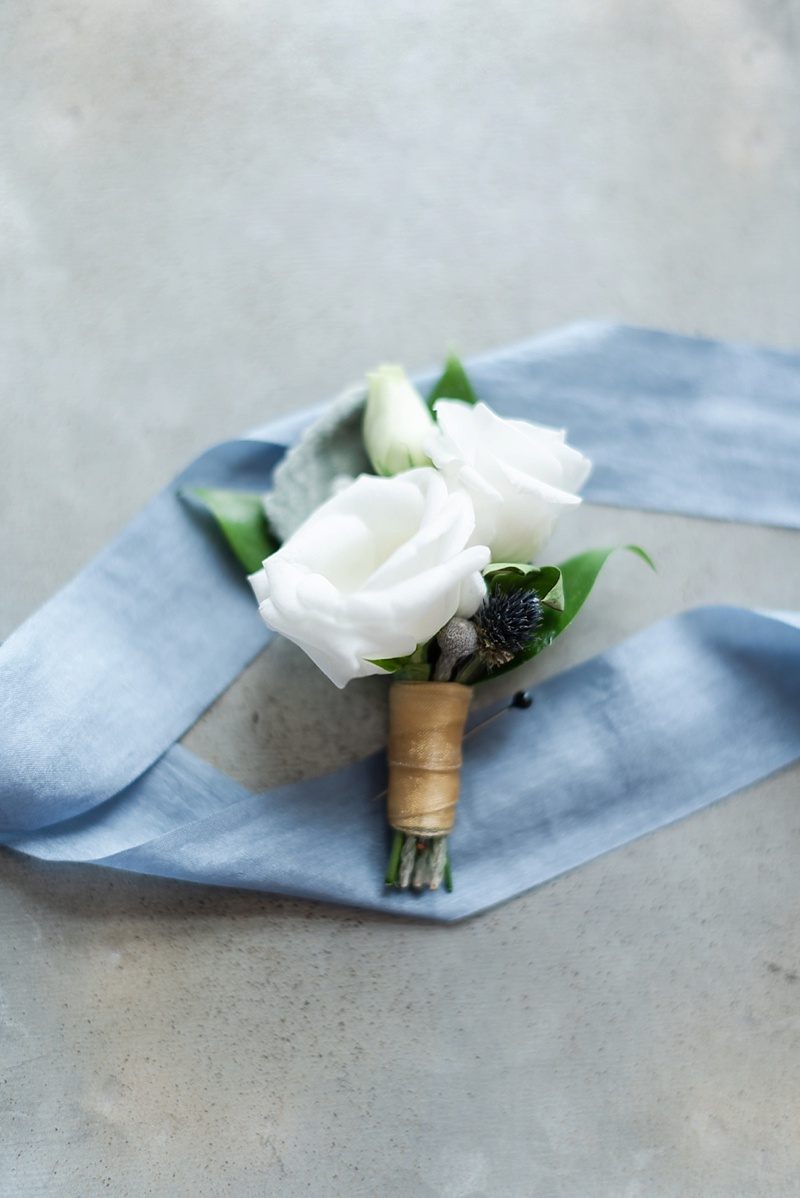 Sweet and small white groom boutonniere with tiny blue thistle for an elegant elopement
