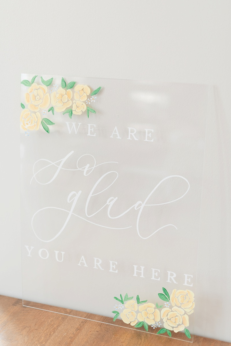 Clear transparent acrylic wedding welcome sign with yellow floral illustrations and white calligraphy