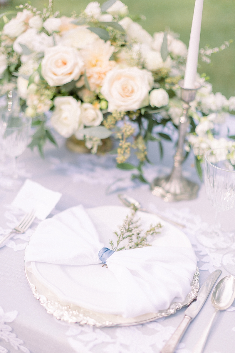 Simple garden wedding table setting with sprig of flowers and blue ribbon napkin ring