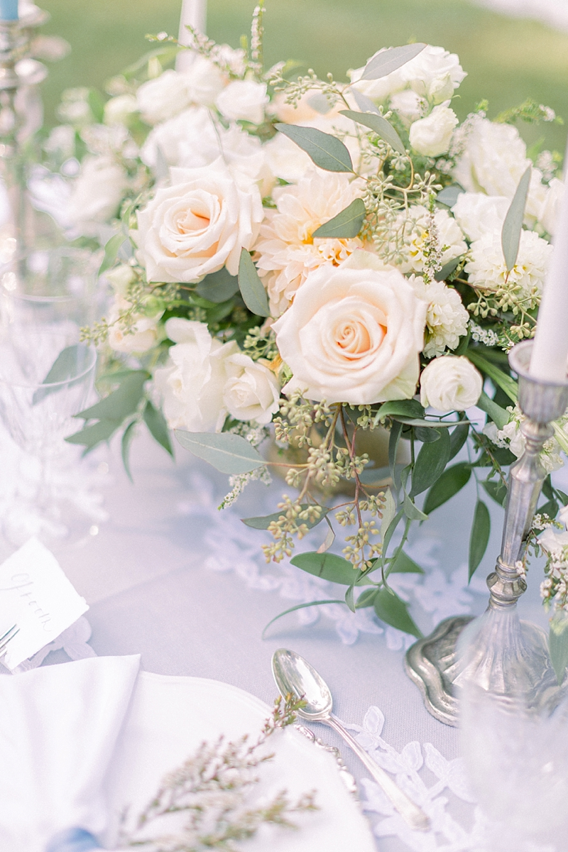Lush low wedding floral centerpiece with pink and peach roses and seeded eucalyptus