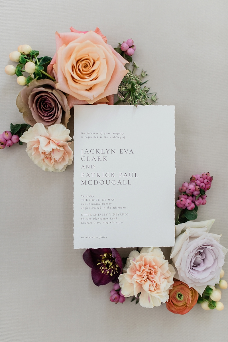 Modern timeless wedding invitation with classic gray typography and deckled paper edges surrounded by wedding flowers