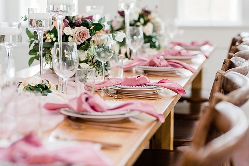 Farm table reception wedding ideas with pink knotted napkins and low floral centerpieces and wooden x back chairs