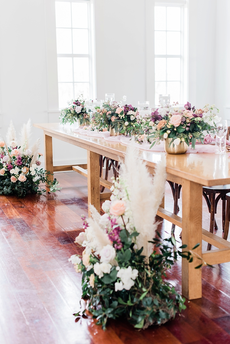 Farm head table for wedding party decorated with pampas grass floral arrangements and high low glass candleholders