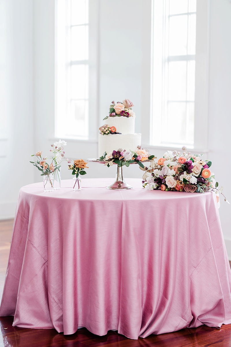 Two tiered deckled edge white wedding cake decorated with fig and peach flowers like ranunculus and hellebore on pink tablecloth
