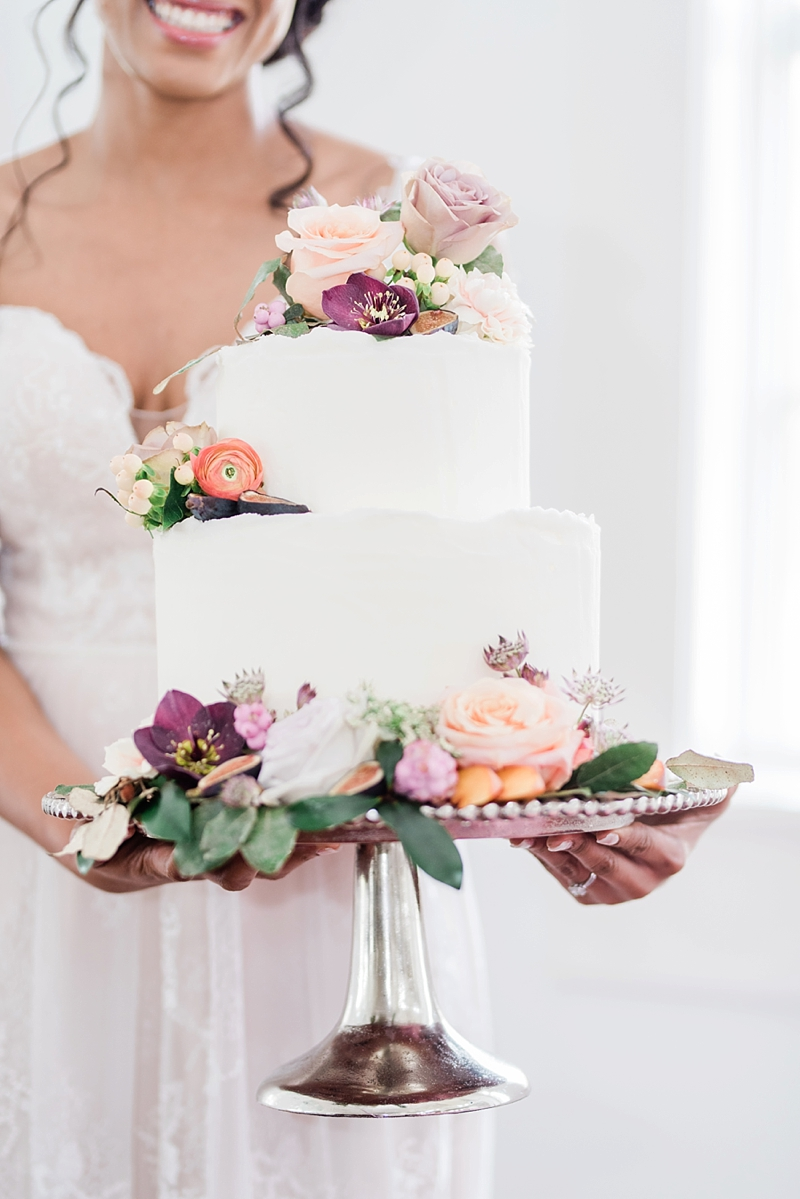 Two tiered deckled edge white wedding cake decorated with fig and peach flowers like ranunculus and hellebore