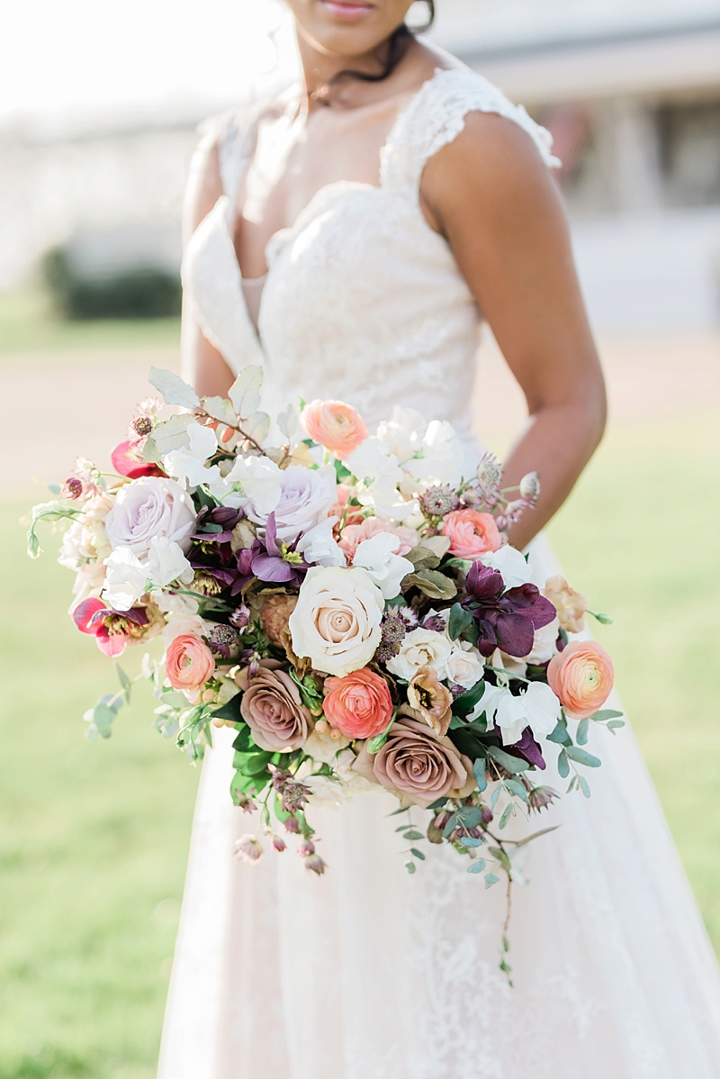 Lush colorful cascade style wedding bouquet with peach and pink colors in roses ranunculus hellebore and sweetpeas
