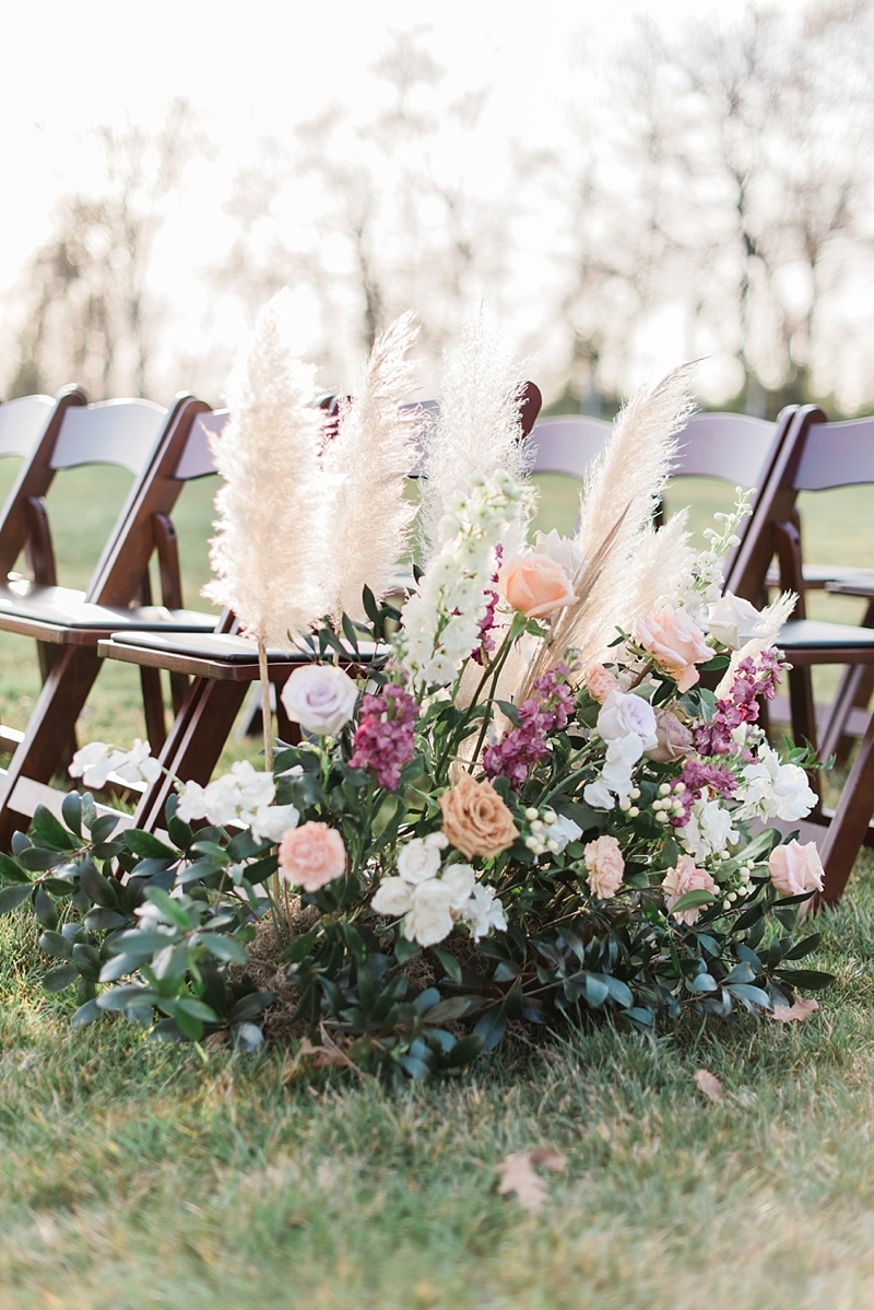Lush wedding ceremony aisle decoration with tall pampas grass and peach and purple flowers in Virginia
