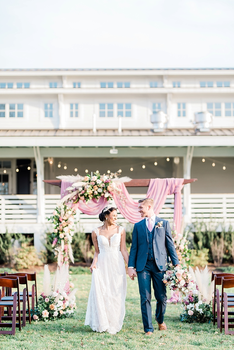 Gorgeous outdoor wedding ceremony with draped arch and pampas grass flowers at Upper Shirley Vineyard in Richmond Virginia