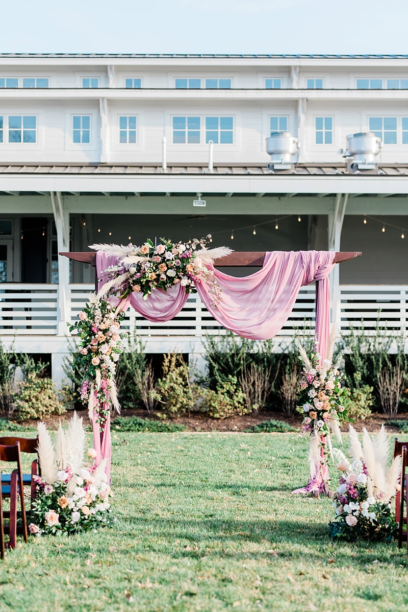 Pink draped outdoor wedding ceremony arch with pampas grass and floral decor at Upper Shirley Vineyard in Virginia