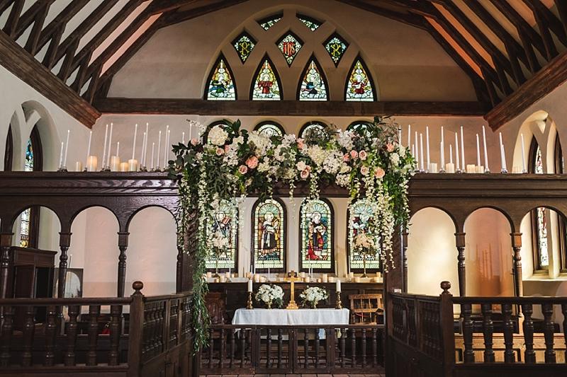 Gorgeous draping wedding florals for indoor ceremony altar at Historic St Lukes Church in Virginia