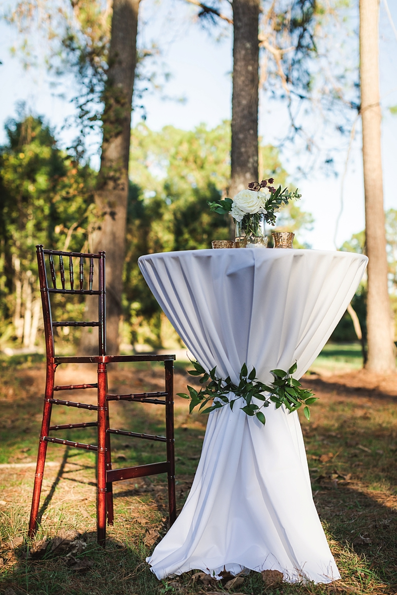 Tall cocktail table with greenery tie detail and metallic mercury votive candles