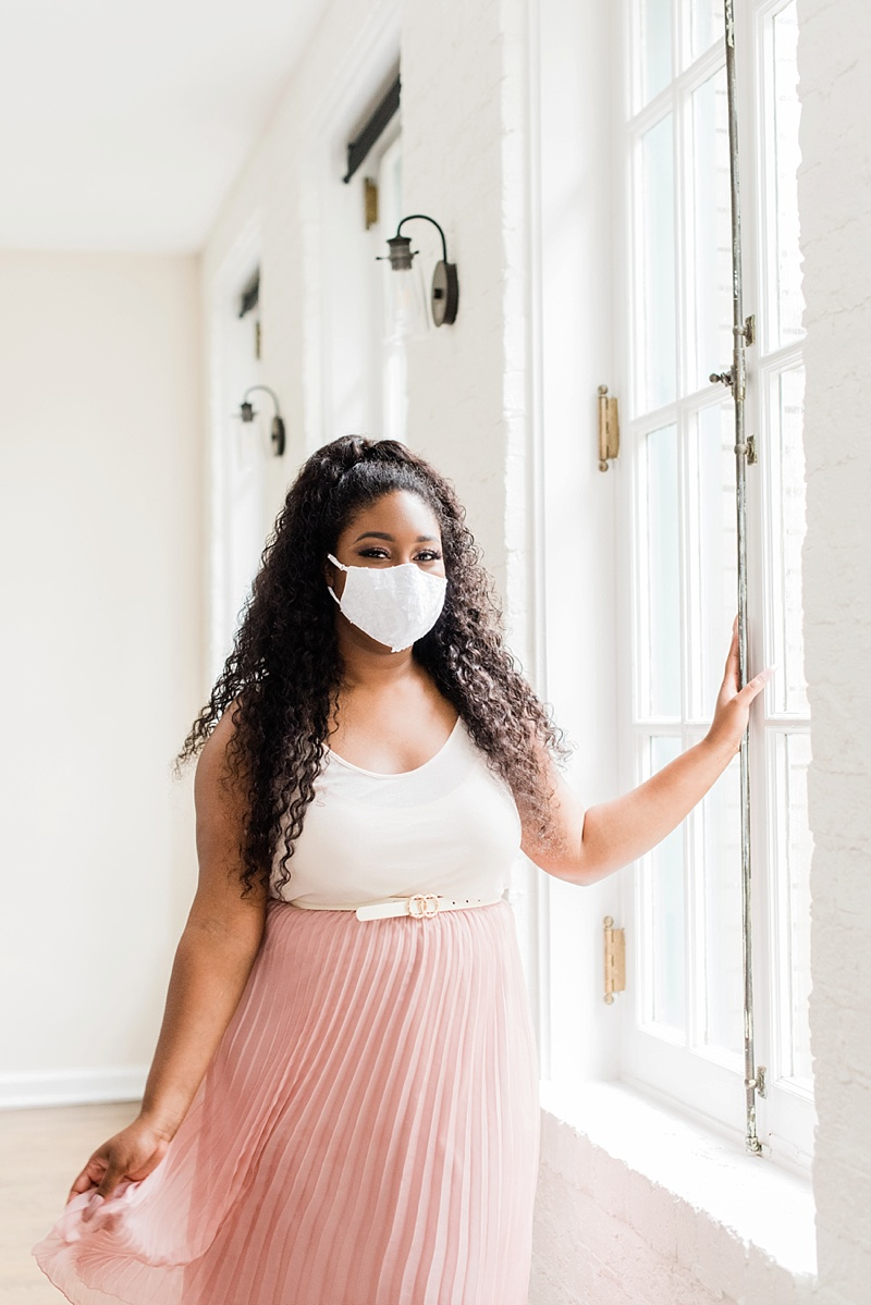 Beautiful Black bride with bridal lace face mask and pleated pink skirt
