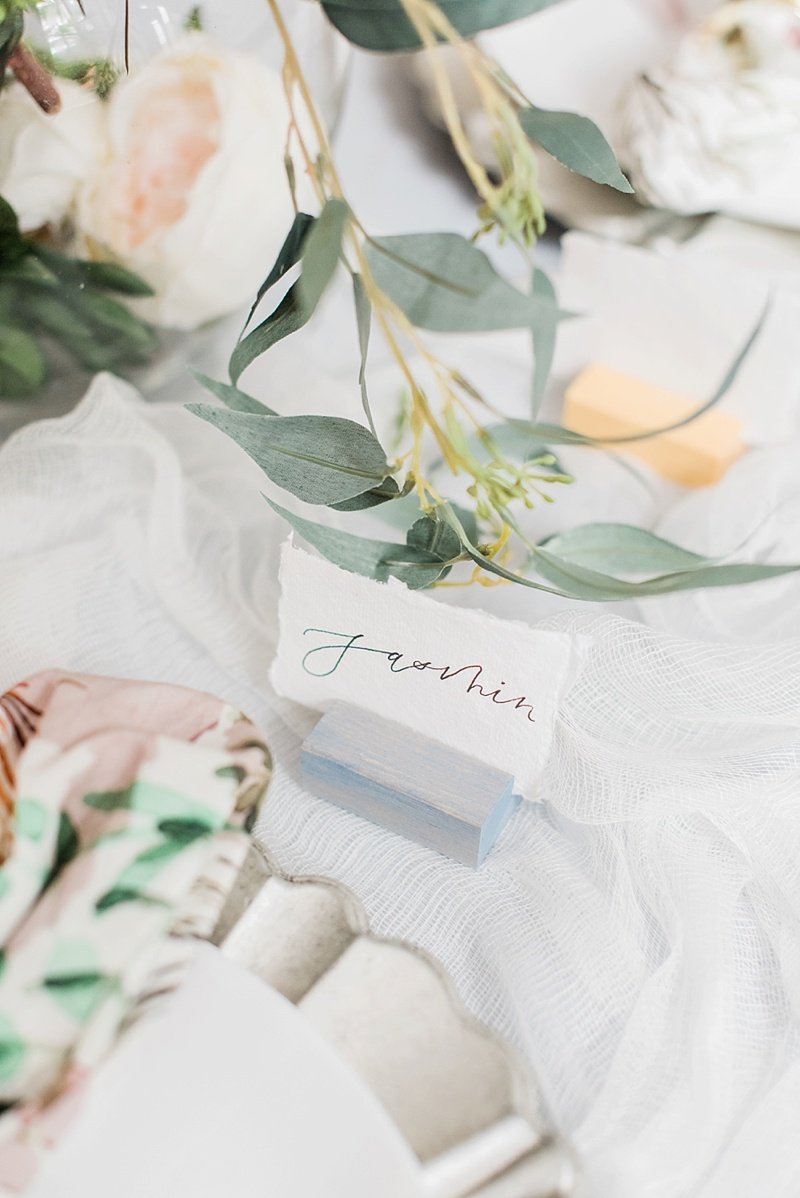 Wooden color-stained wedding bridal shower place card holders with modern calligraphy on handmade paper for chic table setting