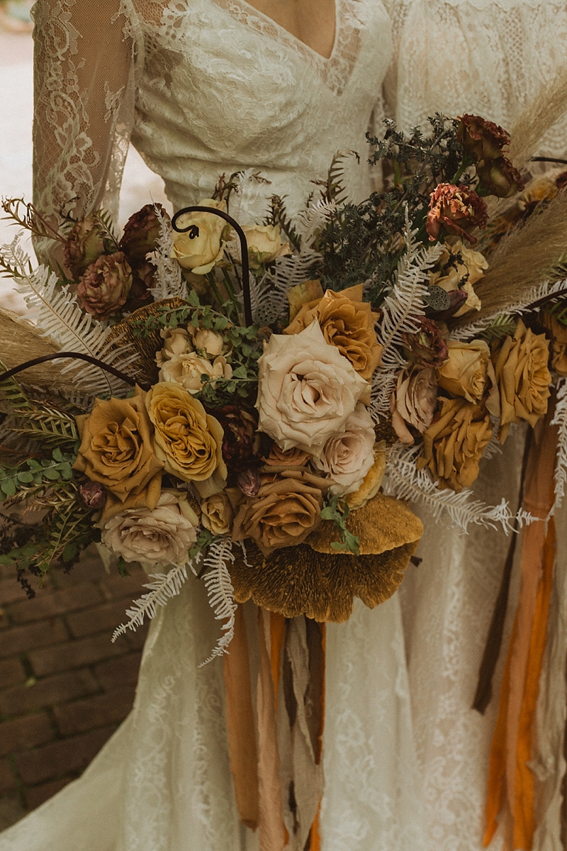 Bohemian wedding bouquet filled with yellow roses and dried sponge mushroom