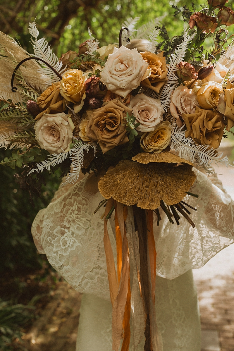 Bohemian wedding bouquet filled with yellow roses and dried sponge mushroom and wrapped in mustard yellow ribbons