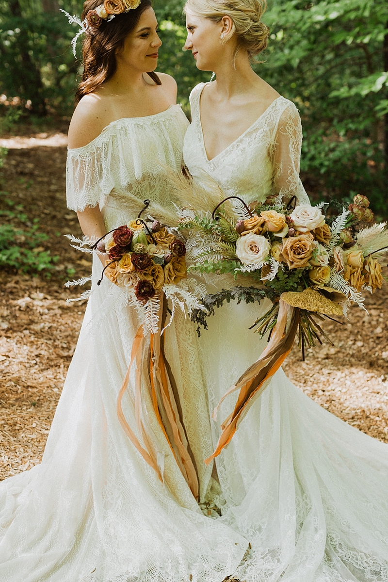 Off shoulder lace wedding dress and second bridal gown with long sleeves for gorgeous lesbian brides in a boho wedding