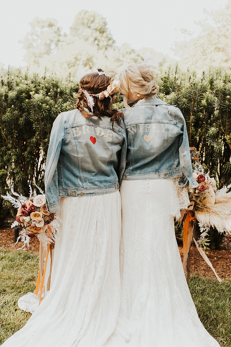 Two beautiful brides wearing adorable custom jean jackets for their wedding