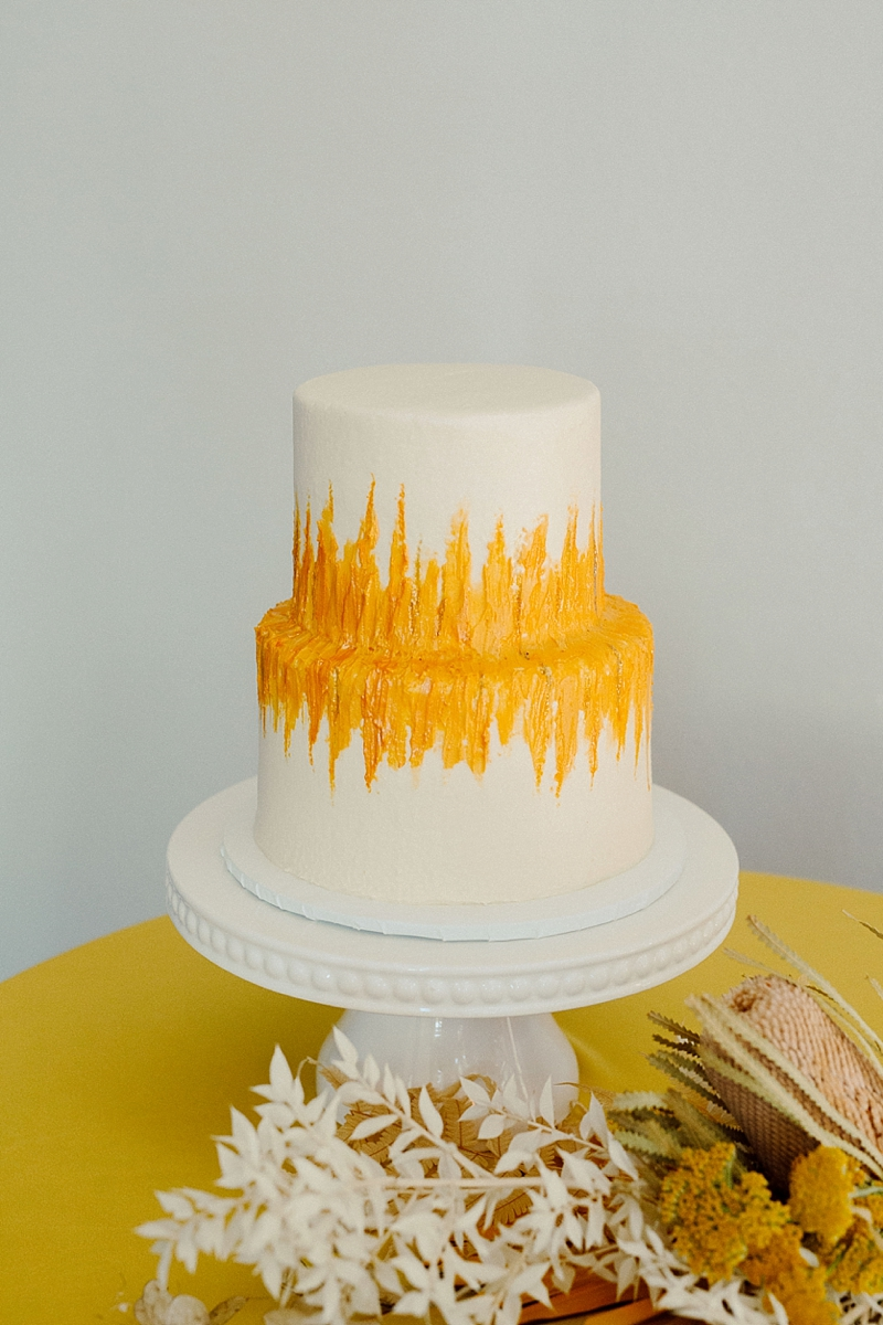 Simple two tiered white wedding cake with yellow painted decoration for boho chic wedding day