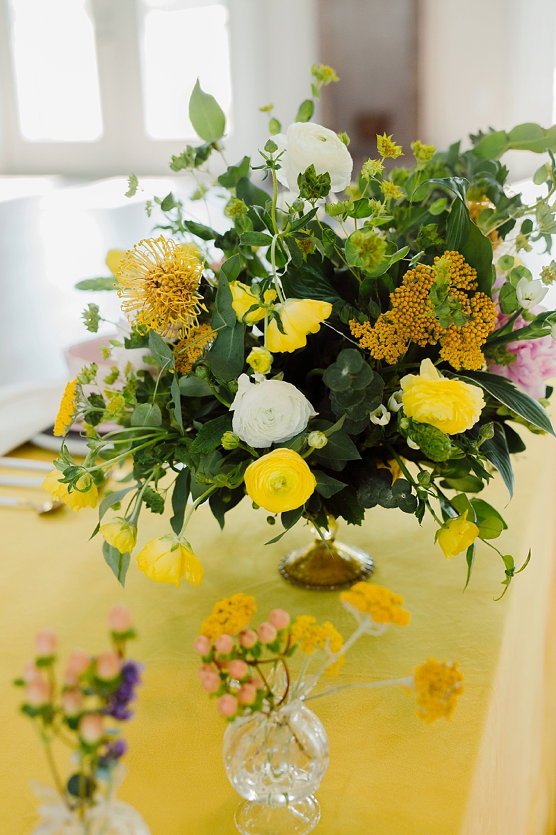 Yellow and white wedding floral centerpiece with ranunculus and pincushion protea