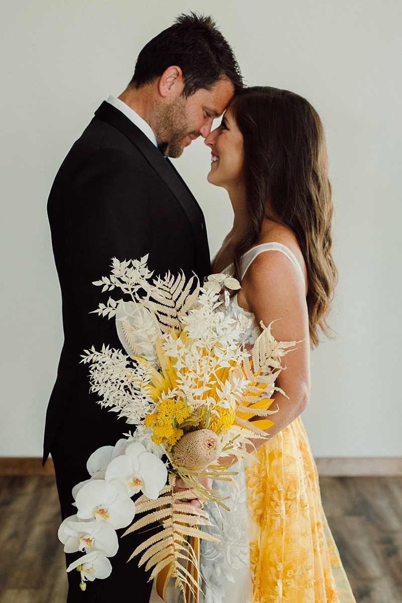 Big boho tropical wedding bouquet with orchids proteas and dried palm leaves
