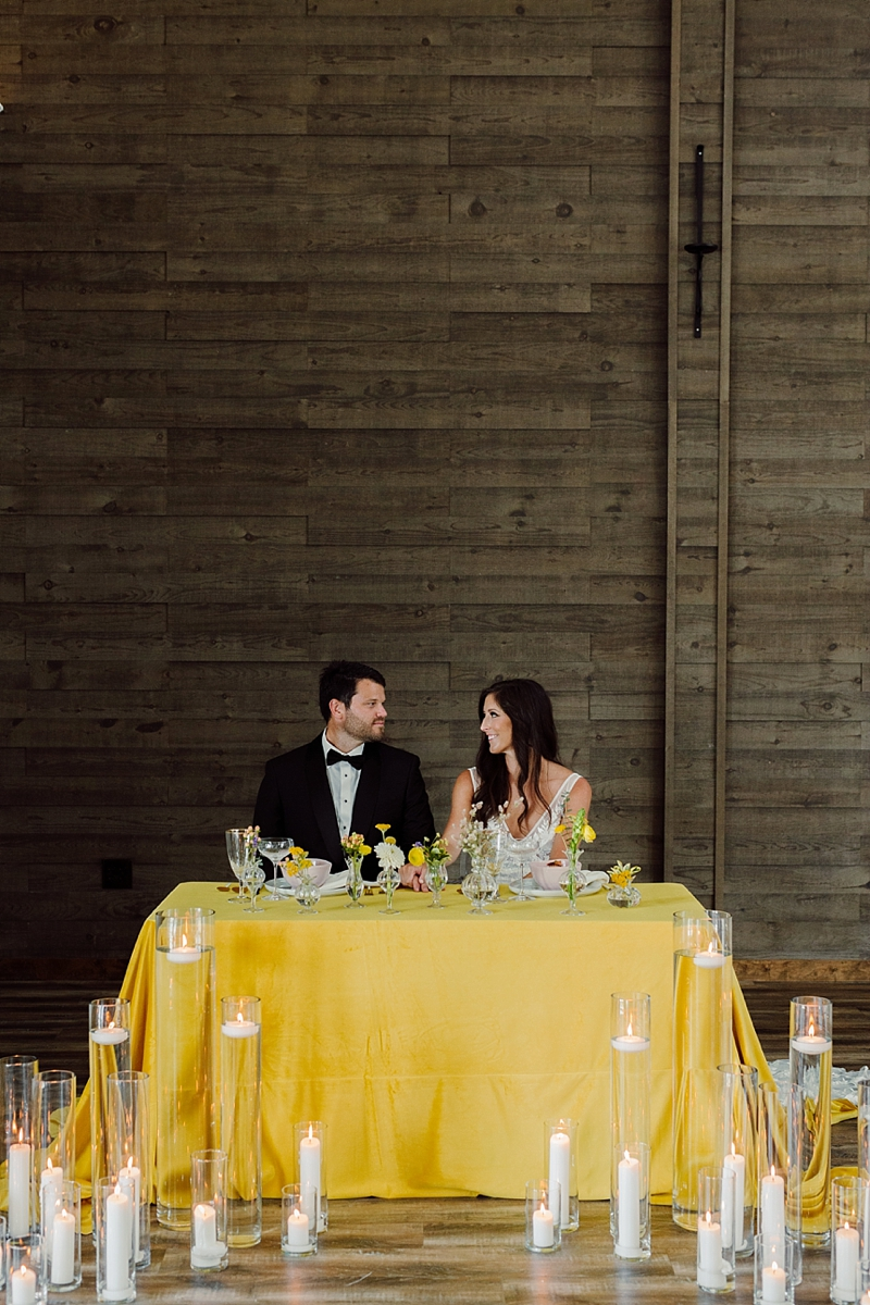 Intimate wedding sweetheart table with yellow tablecloth and lots of pillar candles for boho tropical style
