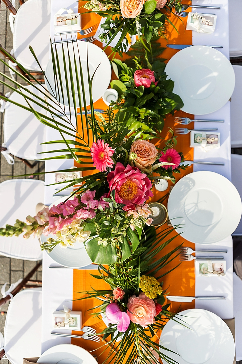 Bright and colorful tropical wedding reception table decor with pink orange and green colors by Virginia Beach based wedding florist