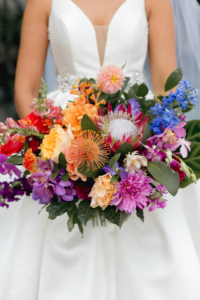 Bright cheerful rainbow wedding bouquet with protea and dahlias by Palette of Petals Virginia Beach florist